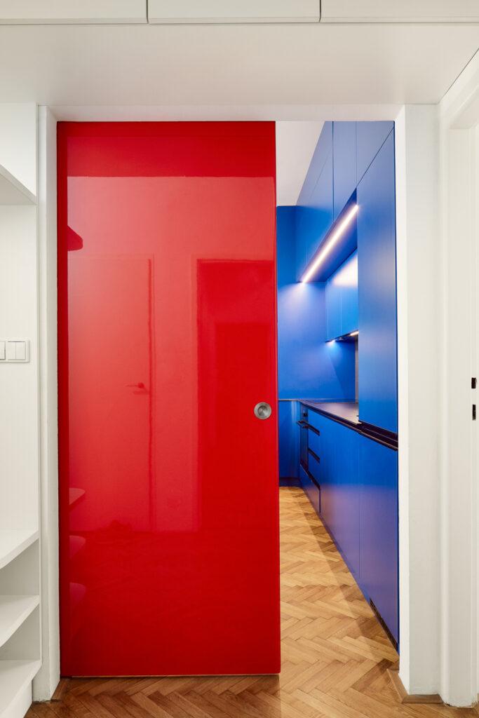 Výrazné červeno-kovové posuvné dveře vytváří kontrast s novou kuchyní. Foto Peter Fabo