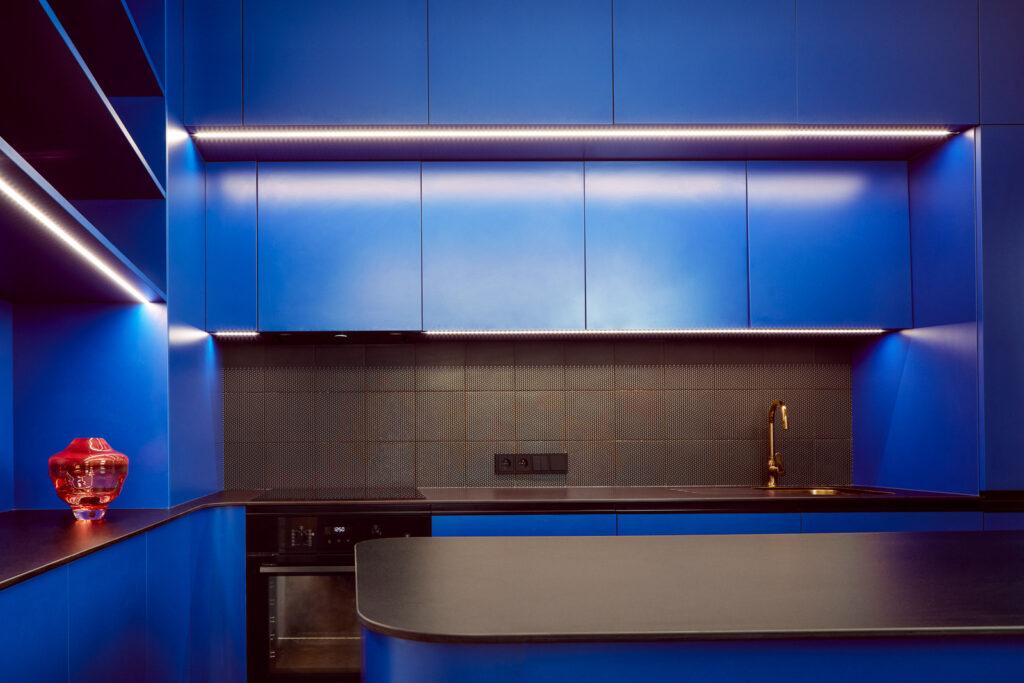 Sytě modro-černá kuchyně tvoří dominantní prvek interiéru letenského bytu. Kuchyni doplňuje výrazně barevná váza sklářského výtvarníka Františka Jungvirta. Foto Peter Fabo