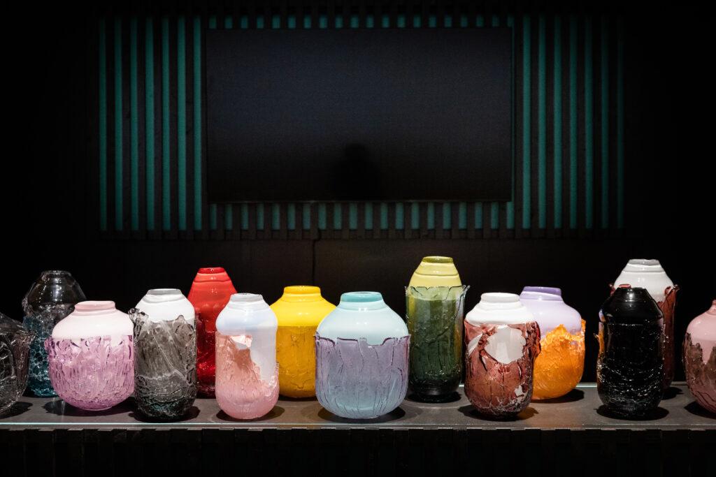 """Studio Davida Valnera se zaměřuje na tvorbu originálních užitých předmětů a uměleckých objektů ze skla zpracovaných tradičními sklářskými technikami. Zatímco loni se na Designbloku staly tahákem jeho houbovité vázičky Fungus, letos v rámci projektu Renesance 21 v UPM zaujal kolekcí barevně hravých """"loupajících"""" váz Recovered. Foto Tomáš Hercog"""